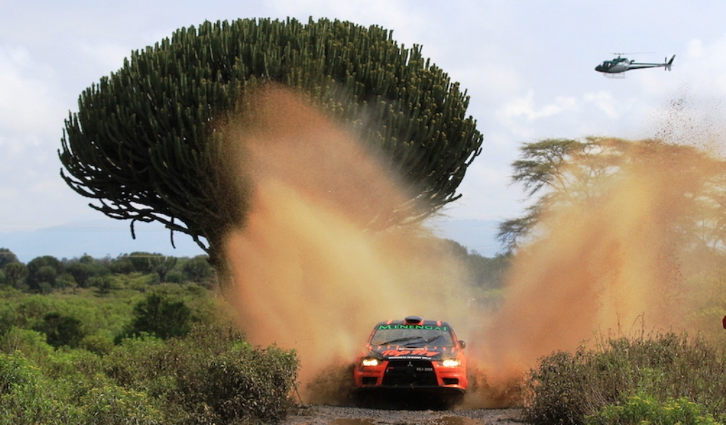 Carl Tundo splashes through a section in Kedong', Naivasha during the 2018 Safari Rally observed by FIA officials