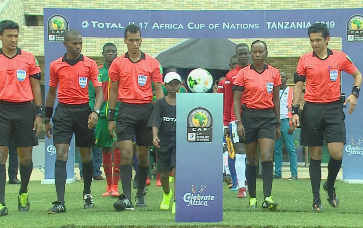 Top: The teams line up for the anthems before the kick-off at the National Stadium, Dar es Salaam on Sunday. Above, match officials lead out the teams