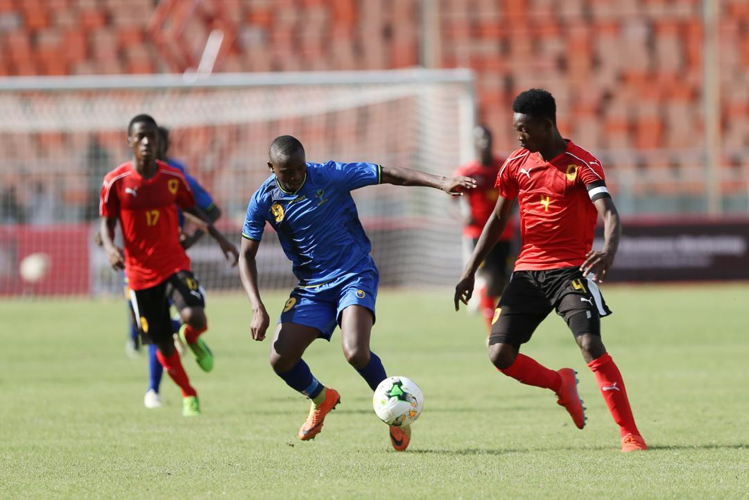 Tanzania forward Edmund John (No. 9) and Angola captain Domingos (right) battle it out at the National Stadium, Dar es Salaam on Saturday
