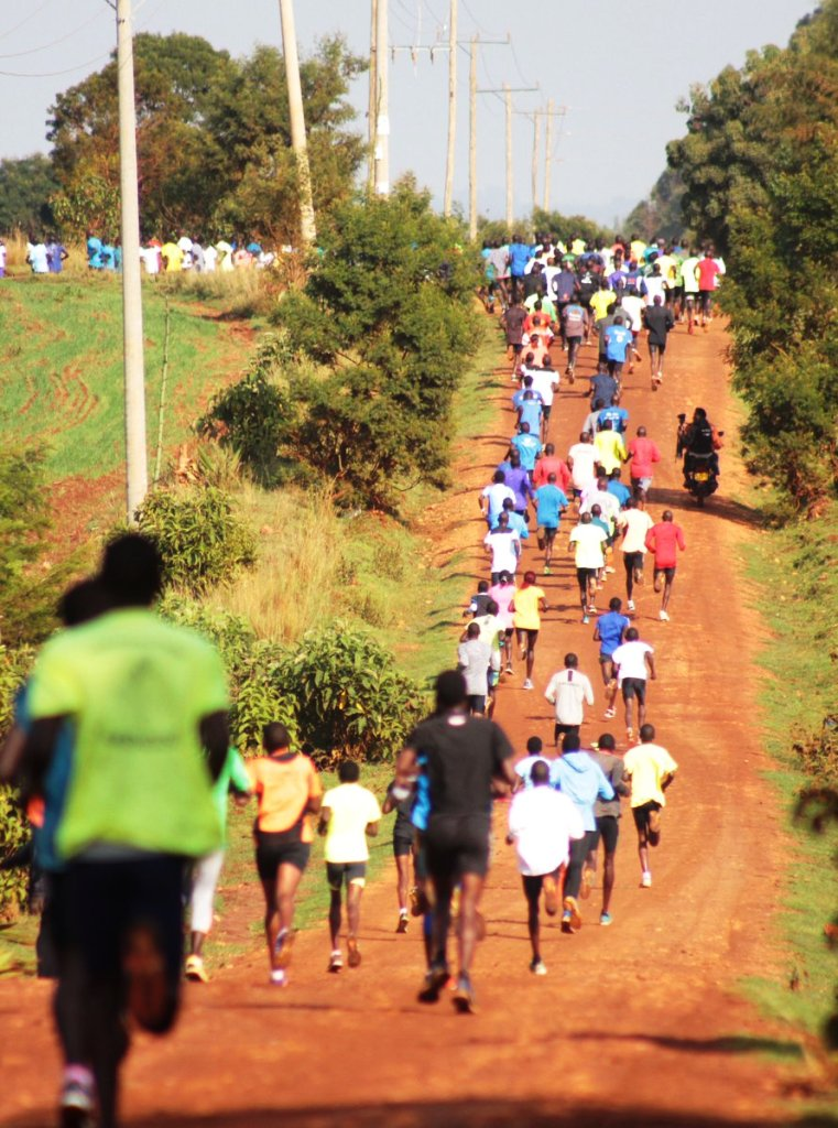 Top: Visiting athletes to Kenya's 'Mecca' of long distance training relax at the gardens Kerio View Hotel in Iten, Elgeyo Marakwet County. Above: A mass of aspiring athletes break into a mid-morning run on the busy farm tracks around Iten