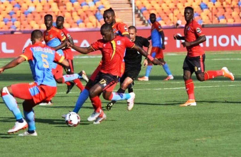 Farouq Miya (No. 17) backed by compatriot Khalid Aucho (right) takes on DR Congo's Marcel Tisserand (left) in Cairo