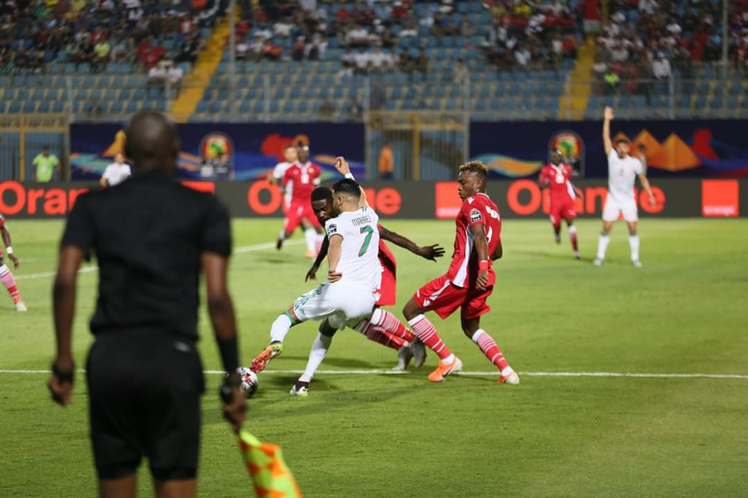 Top: Kenya's Dennis OMINO (No 21), Abud OMAR (No. 3) and Musa Mohammed (No. 5) beaten to the race by Algeria in their match in Cairo on Sunday. Above: Kenyans try to deal with red-hot Algeria's Manchester City forward Riyad Mahrez (No. 7)