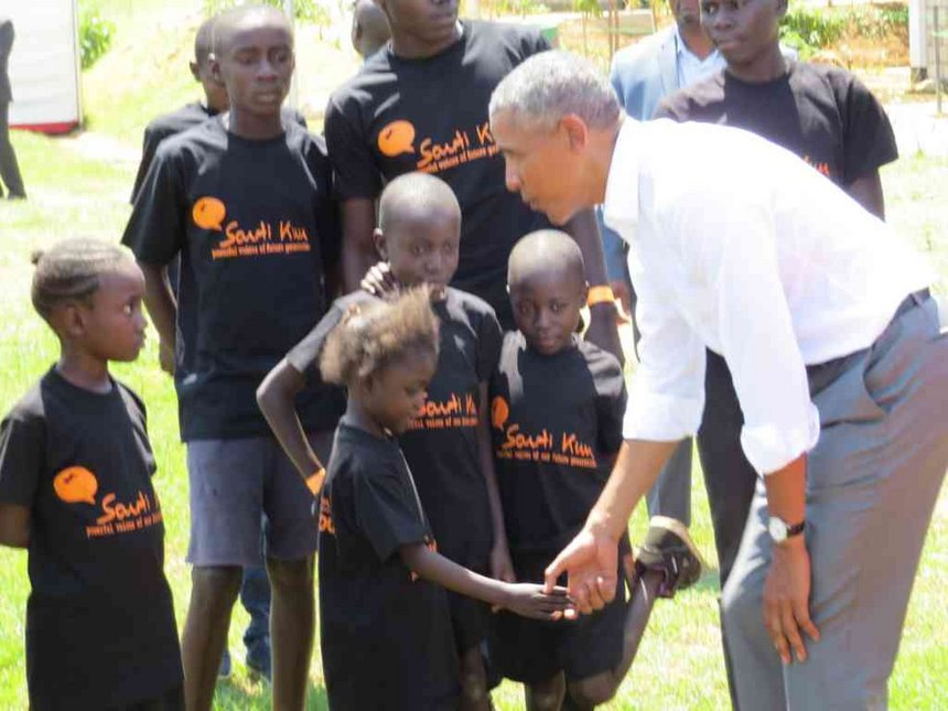 President of the United States Barrack Obama makes a shot at a facility in Kogelo, Siaya County, his father's birth place. Below, POTUS Obama with children in Kogelo where he initiated a youth development and sports programme 'Sauti Kuu'