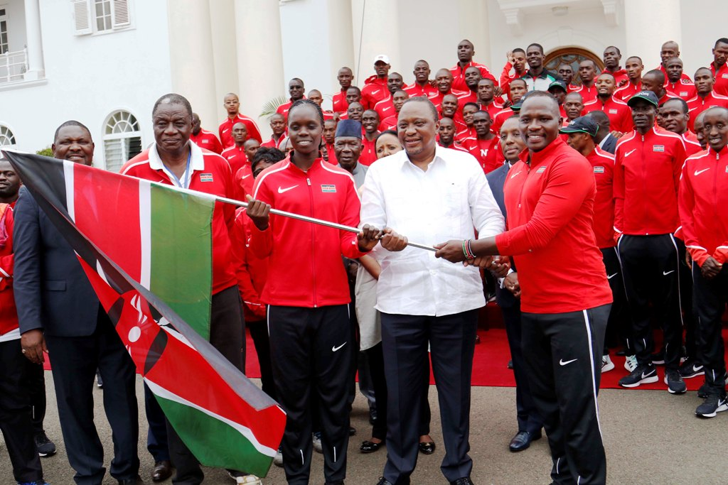 President Kenyatta (2nd right) hands flag to Team Kenya captains Julius Yego (right), Mercy Moim (3rd from right). Chief executive officer Charles Nyaberi is 2nd from left, deputy chief de mission Shadrack Maluki (left) at State House on Monday, wishing them success in Morocco. Photo/MOHMMED AMIN